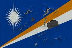 Κλείστε επάνω τη βρώμικη, χαλασμένη και ξεπερασμένη σημαία Νησιών Μάρσαλ στην αποφλοίωση τοίχων από το χρώμα για να δείτε την εσω στοκ εικόνες