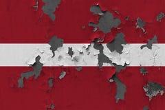 Κλείστε επάνω τη βρώμικη, χαλασμένη και ξεπερασμένη σημαία της Λετονίας στην αποφλοίωση τοίχων από το χρώμα για να δείτε την εσωτ στοκ εικόνα