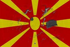 Κλείστε επάνω τη βρώμικη, χαλασμένη και ξεπερασμένη σημαία της Μακεδονίας στην αποφλοίωση τοίχων από το χρώμα για να δείτε την εσ στοκ εικόνα με δικαίωμα ελεύθερης χρήσης