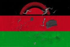Κλείστε επάνω τη βρώμικη, χαλασμένη και ξεπερασμένη σημαία του Μαλάουι στην αποφλοίωση τοίχων από το χρώμα για να δείτε την εσωτε στοκ εικόνες