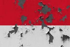 Κλείστε επάνω τη βρώμικη, χαλασμένη και ξεπερασμένη σημαία του Μονακό στην αποφλοίωση τοίχων από το χρώμα για να δείτε την εσωτερ στοκ φωτογραφία