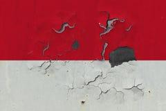Κλείστε επάνω τη βρώμικη, χαλασμένη και ξεπερασμένη σημαία του Μονακό στην αποφλοίωση τοίχων από το χρώμα για να δείτε την εσωτερ στοκ εικόνα