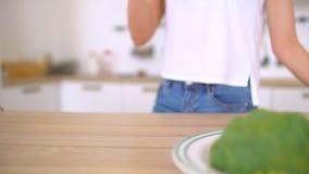 Κλείστε επάνω τη γυναίκα πίσω από την κουζίνα λεσχών υγείας που πίνει τον εύγευστο υγιή φυτικό καταφερτζή - θηλυκά λεσχών υγείας απόθεμα βίντεο