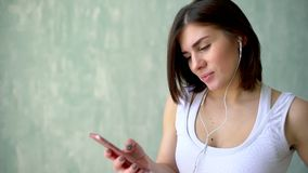 Κλείστε επάνω τη γυναίκα πορτρέτου με τα ακουστικά που ακούει τη μουσική μετά από το σκληρό workout στη γυμναστική Χαλάρωση κοριτ απόθεμα βίντεο