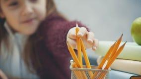 Κλείστε επάνω τη μαθήτρια σε ένα γκρίζο υπόβαθρο Κατά τη διάρκεια αυτής της περιόδου κάθεται στον πίνακα Παίρνοντας ένα μολύβι σύ φιλμ μικρού μήκους