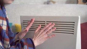 Κλείστε επάνω τη νέα γυναίκα παγώνει στο καθιστικό και θερμαίνεται δίπλα σε μια ηλεκτρική θερμάστρα φιλμ μικρού μήκους
