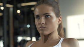 Κλείστε επάνω τη νέα γυναίκα που κάνει τη γυμναστική βαρών στον εκπαιδευτή στη healty λέσχη φιλμ μικρού μήκους
