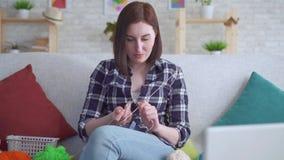 Κλείστε επάνω τη συνεδρίαση γυναικών στον καναπέ μπροστά από ένα lap-top μαθαίνοντας να πλέκει απόθεμα βίντεο