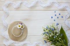 Κλείστε επάνω τη φωτογραφία με λίγο καπέλο, κρίνοι της κοιλάδας, και της δαντέλλας σε ένα άσπρο ξύλινο υπόβαθρο, τοπ άποψη στοκ εικόνες με δικαίωμα ελεύθερης χρήσης