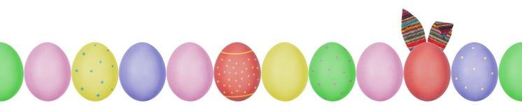 Κλείστε επάνω τη φωτογραφία των ζωηρόχρωμων χρωματισμένων αυγών Πάσχας με eggshell τη σύσταση που τακτοποιείται σε μια σειρά Ένα  στοκ εικόνες