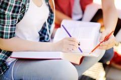 Κλείστε επάνω τη φωτογραφία των νέων ευτυχών σπουδαστών με τα βιβλία και τις σημειώσεις υπαίθρια Στοκ Εικόνες