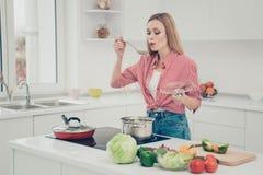 Κλείστε επάνω τη φωτογραφία όμορφη αυτή η κυρία της προετοιμάζει το εύγευστο γεύμα πιάτων δοκιμάζει τον αλμυρό αέρα χτυπήματος γο στοκ φωτογραφίες
