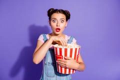 Κλείστε επάνω τη φωτογραφία όμορφη που καταπλήσσει αυτή η κυρία της που δύο TV ρολογιών κουλουριών παρουσιάζουν popcorn λαβής στα στοκ εικόνες