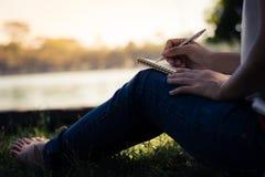 κλείστε επάνω τις νέες γυναίκες που γράφουν στο σημειωματάριο στο πάρκο, έννοια στο edu Στοκ φωτογραφία με δικαίωμα ελεύθερης χρήσης