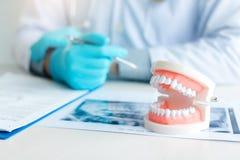 Κλείστε επάνω τις οδοντοστοιχίες με τον οδοντίατρο που εργάζεται στον πίνακα στην κλινική στοκ φωτογραφία με δικαίωμα ελεύθερης χρήσης
