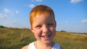 Κλείστε επάνω τις συγκινήσεις του αγοριού με την ευτυχή έκφραση στο πρόσωπο Πορτρέτο του ευτυχούς κόκκινου αγοριού τρίχας με τα γ απόθεμα βίντεο