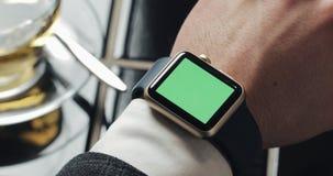 Κλείστε επάνω τις χειρονομίες χεριών ατόμων σε μια σύγχρονη χρήση smartwatch με μια πράσινη οθόνη στον καφέ Ένα φλυτζάνι του τσαγ φιλμ μικρού μήκους