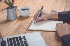 Κλείστε επάνω τον επιχειρηματία γράφει το σημειωματάριο και χρησιμοποίηση του lap-top στην ξύλινη ετικέττα Στοκ φωτογραφία με δικαίωμα ελεύθερης χρήσης