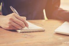 Κλείστε επάνω τον επιχειρηματία γράφει το σημειωματάριο και χρησιμοποίηση του lap-top στον ξύλινο πίνακα Στοκ Εικόνες