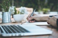Κλείστε επάνω τον επιχειρηματία γράφει το σημειωματάριο και χρησιμοποίηση του lap-top στον ξύλινο πίνακα Στοκ Φωτογραφία