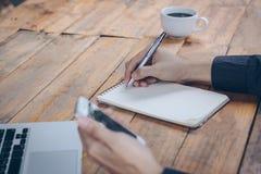 Κλείστε επάνω τον επιχειρηματία γράφει το σημειωματάριο και χρησιμοποίηση του τηλεφώνου κυττάρων Στοκ Εικόνες