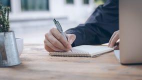Κλείστε επάνω τον επιχειρηματία γράφει το σημειωματάριο και χρησιμοποίηση του lap-top Στοκ Εικόνα