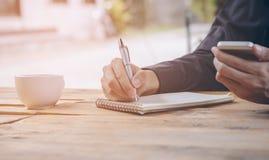 Κλείστε επάνω τον επιχειρηματία γράφει το σημειωματάριο και χρησιμοποίηση του κινητού τηλεφώνου Στοκ φωτογραφία με δικαίωμα ελεύθερης χρήσης