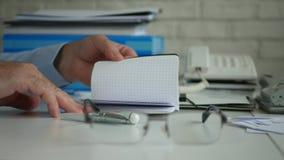 Κλείστε επάνω τον επιχειρηματία παραδίδει το γραφείο που ψάχνει τις πληροφορίες σε μια μικρή ημερήσια διάταξη απόθεμα βίντεο