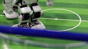 Κλείστε επάνω του έξυπνου ποδιού ρομπότ humanoid που θερμαίνει στο αγωνιστικό χώρο ποδοσφαίρου απόθεμα βίντεο
