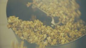 Κλείστε επάνω του ανακατώματος popcorn στο κύπελλο στο εργοστάσιο 4K απόθεμα βίντεο
