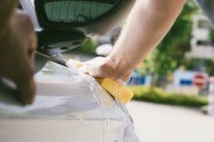 Κλείστε επάνω του αρσενικού καθαρίζοντας αυτοκινήτου χεριών με το σφουγγάρι στοκ εικόνες