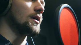Κλείστε επάνω του αρσενικού τραγουδιστή στα ακουστικά που τραγουδούν το τραγούδι στο μικρόφωνο στο υγιές στούντιο Νεαρός άνδρας π απόθεμα βίντεο