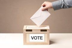 Κλείστε επάνω του αρσενικού χεριού βάζοντας την ψηφοφορία σε ένα κάλπη Στοκ Εικόνα
