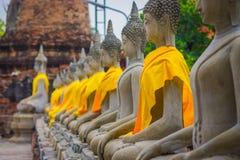 Κλείστε επάνω του αρχαίου αγάλματος του Βούδα σε μια σειρά με ένα κίτρινο ύφασμα σε WAT YAI CHAI MONGKOL, η ιστορική πόλη Ayuttha Στοκ Εικόνες