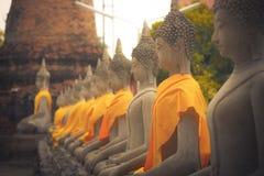 Κλείστε επάνω του αρχαίου αγάλματος του Βούδα σε μια σειρά με ένα κίτρινο ύφασμα σε WAT YAI CHAI MONGKOL, η ιστορική πόλη Ayuttha Στοκ Εικόνα