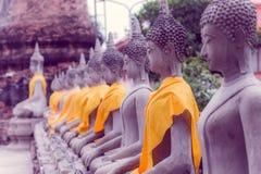 Κλείστε επάνω του αρχαίου αγάλματος του Βούδα σε μια σειρά με ένα κίτρινο ύφασμα σε WAT YAI CHAI MONGKOL, η ιστορική πόλη Ayuttha Στοκ φωτογραφία με δικαίωμα ελεύθερης χρήσης