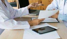 κλείστε επάνω του ασθενή και του γιατρού που παίρνουν τις σημειώσεις ή το επαγγελματικό medi στοκ φωτογραφίες