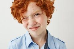 Κλείστε επάνω του αστείου αγοριού πιπεροριζών με τις φακίδες και τα κόκκινα μάγουλα παρεκκλίνουν το μάτι λόγω της φωτεινής αστραπ στοκ φωτογραφίες με δικαίωμα ελεύθερης χρήσης