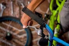 Κλείστε επάνω του ατόμου που καθορίζει handlebar του ποδηλάτου, σε ένα εργαστήριο Στοκ Εικόνες
