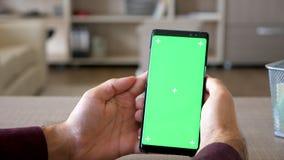 Κλείστε επάνω του ατόμου που κοιτάζει βιαστικά το Διαδίκτυο στο smartphone με την πράσινη χλεύη χρώματος οθόνης επάνω φιλμ μικρού μήκους