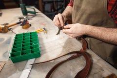 Κλείστε επάνω του βυρσοδέψη χεριών εκτελεί την εργασία για τον πίνακα με τα εργαλεία στοκ εικόνα με δικαίωμα ελεύθερης χρήσης