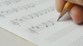 Κλείστε επάνω του γραψίματος μουσικής Μουσικός που συνθέτει με ένα μολύβι: προσωπικό, κλειδί, σημείωση φιλμ μικρού μήκους