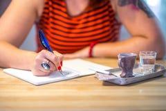 Κλείστε επάνω του γυναικείου χεριού γράφοντας στο σημειωματάριο στο φραγμό coofee στοκ εικόνα