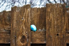 Κλείστε επάνω του διακοσμημένου αυγού με μια καρδιά, που κρύβεται στον ξύλινο φράκτη για το κυνήγι αυγών Πάσχας στο κατώφλι Στοκ Εικόνες
