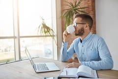 Κλείστε επάνω του ενηλίκου ο σκοτεινός-μαλλιαρός καυκάσιος αρσενικός επιχειρηματίας στο κάθισμα γυαλιών στην αρχή, κοιτάζοντας κα Στοκ εικόνες με δικαίωμα ελεύθερης χρήσης