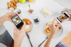 Κλείστε επάνω του ζεύγους με τα smartphones στο πρόγευμα Στοκ φωτογραφία με δικαίωμα ελεύθερης χρήσης