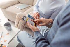 Κλείστε επάνω του ηλικιωμένου ζεύγους που ελέγχει τον καιρό apps στα τηλέφωνα Στοκ φωτογραφίες με δικαίωμα ελεύθερης χρήσης