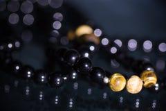 Κλείστε επάνω του ημιπολύτιμου ματιού τιγρών πολύτιμων λίθων και των μαύρων βραχιολιών tourmaline στο μαύρο σχέδιο υποβάθρου Στοκ φωτογραφία με δικαίωμα ελεύθερης χρήσης