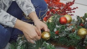 Κλείστε επάνω του θηλυκού σχεδιαστή που χτυπά το στεφάνι Χριστουγέννων μετά από τον εορτασμό απόθεμα βίντεο