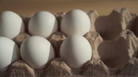 Κλείστε επάνω του θηλυκού χεριού βάζει τα αυγά σε ένα κουτί από χαρτόνι στον πίνακα φιλμ μικρού μήκους